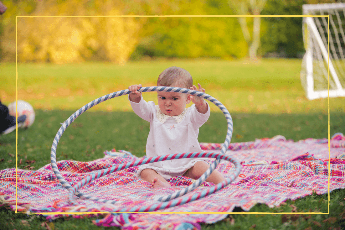 A baby girl sitting on a rug outside playing with a hoola hoop