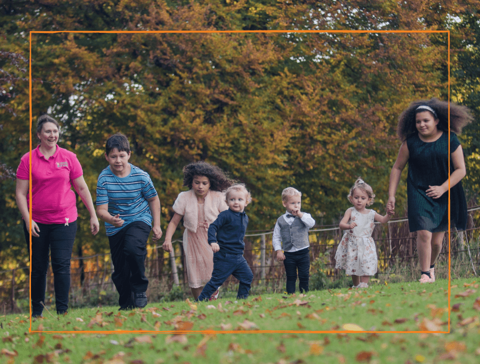 A group of young children are running in a park in Autumn with a childcare provider from Thank Evans